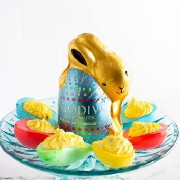 Easter Deviled eggs on a blue cake stand with a chocolate bunny