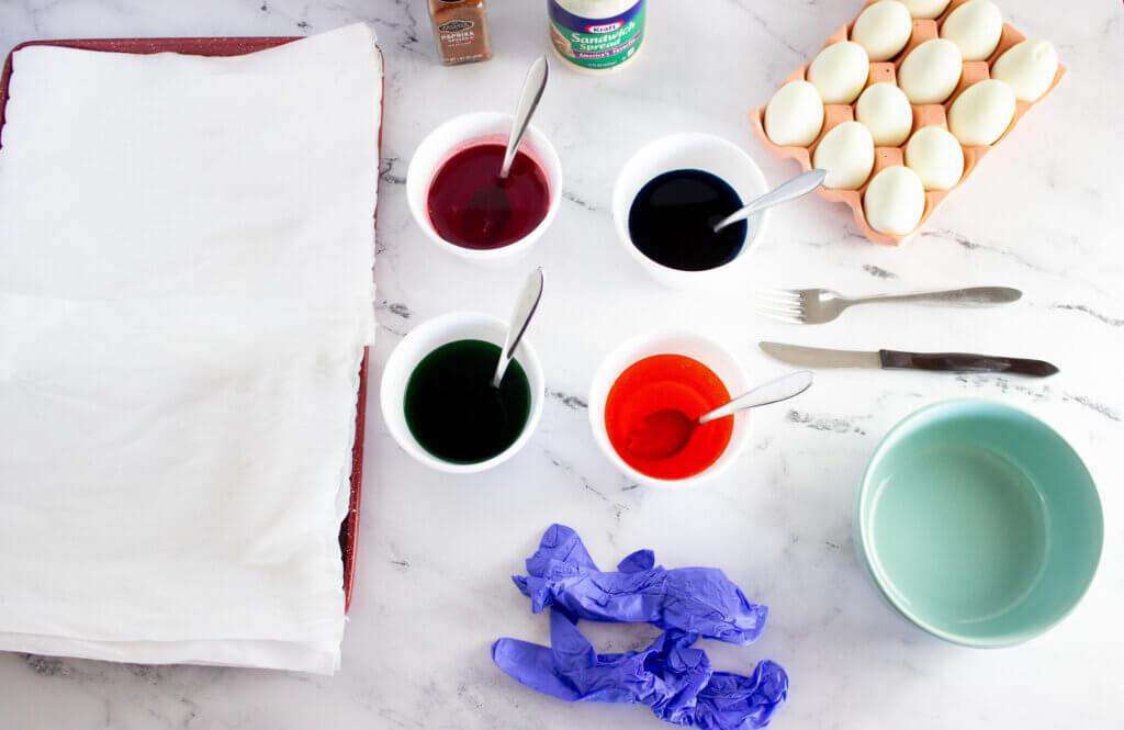 Four cups with food coloring, water, and vinegar to color eggs