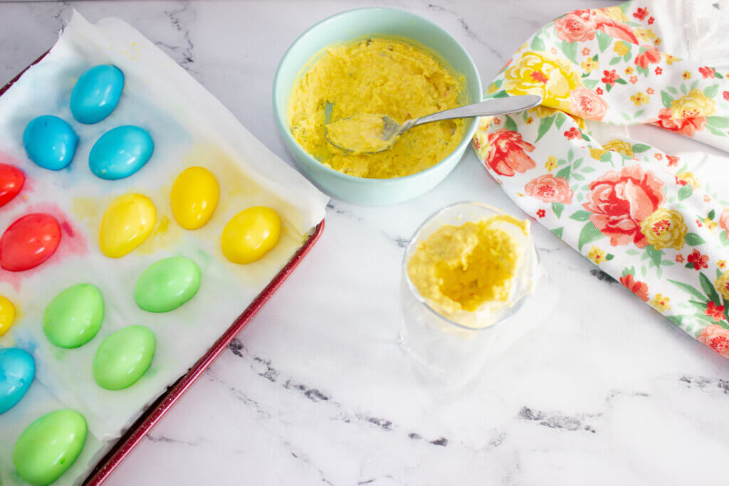 Spooning deviled egg mixture in a piping bag in a glass